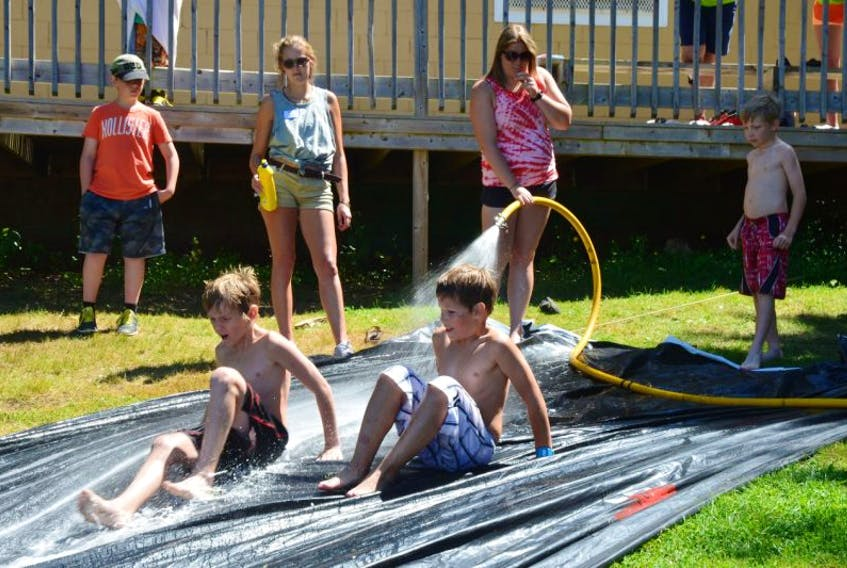 County of Kings summer recreation intern Ashley Brooker keeps the water – and fun – flowing on the soap slide as part of Camp Day.