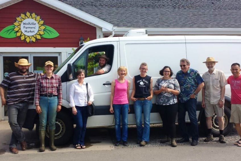 Vendors at the Wolfville Farmers Market stand in front of the new van for deliveries starting next month to three community hubs.