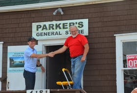 Craig Parker and Dick Killam shake hands after removing the paper from the Parker's General Store sign.