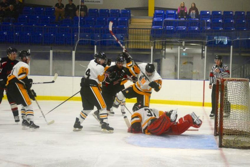 East Hants goalie makes a dive save while Devon Pennell, number 60 with the Avon River Rats races for the puck.