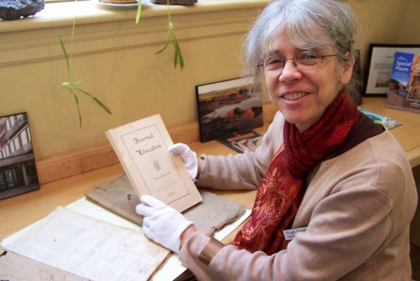 Kate Adams, office manager at the Kings County Museum, examines documents relating to school exercise books used here in the 1840s. The books were recently donated to the museum.