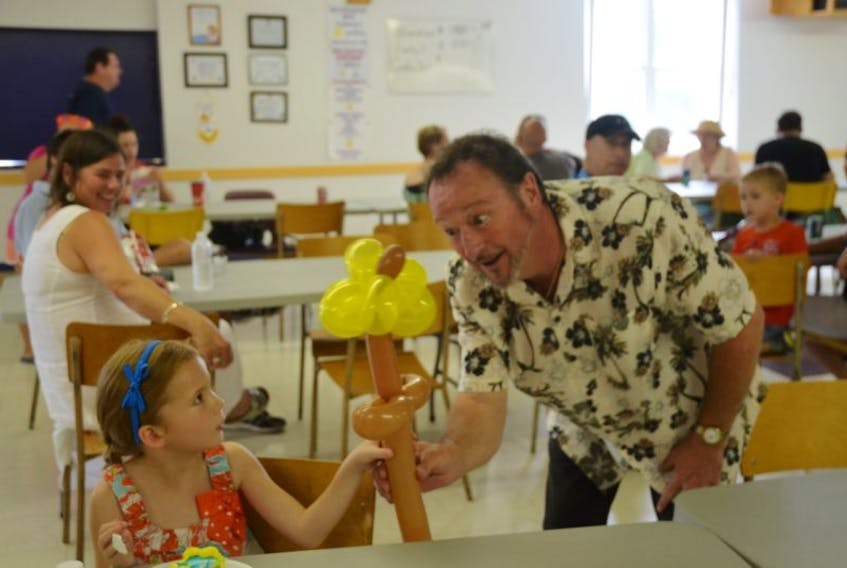 Six-year-old Sylvie Batstone of Canning is pleasantly surprised by Bob Deveau, who made her a flower balloon animal.