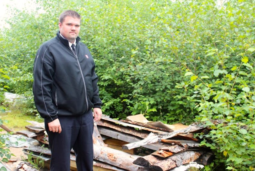 Salvation Army Capt. Brent Haas stands alongside a rough shelter that served as someone's living accommodations last year. Although it doesn't appear anyone still uses it, Haas said there is still work to be done to address housing and homelessness issues in the Upper Lake Melville area, so that shelters such as these don't have to exist.