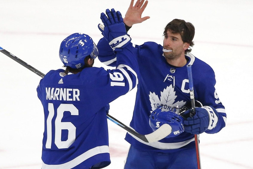 Toronto Maple Leafs John Tavares C (91) congratulates teammate Mitch Marner after their 4-2 win over the Oilers in Toronto on Friday January 22, 2021.