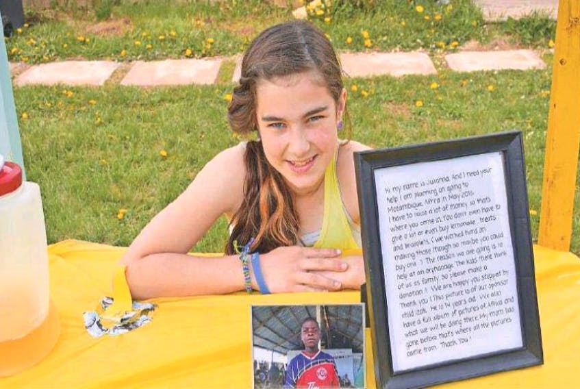 <p>Julianna Gillis, 12, kneels next to the photo of her family's sponsor child and the framed explanation of how the lemonade stand and other fundraisers will help send her and her mother to Africa to meet him.</p>