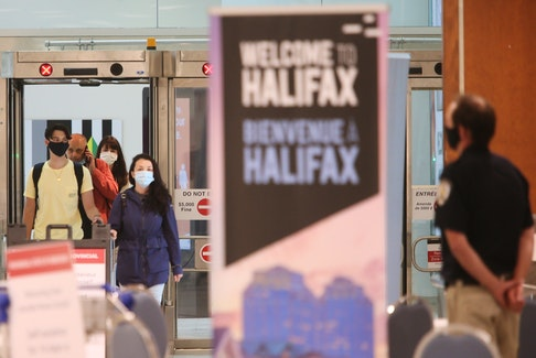 Air passengers arriving from a flight from St. John's speak to a member of provincial heath enforcement staff, in the baggage area of Halifax Stanfield International Airport last week. SALTWIRE FILE PHOTO