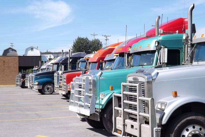 Transport trucks line a parking lot awaiting the arrival of cargo.
