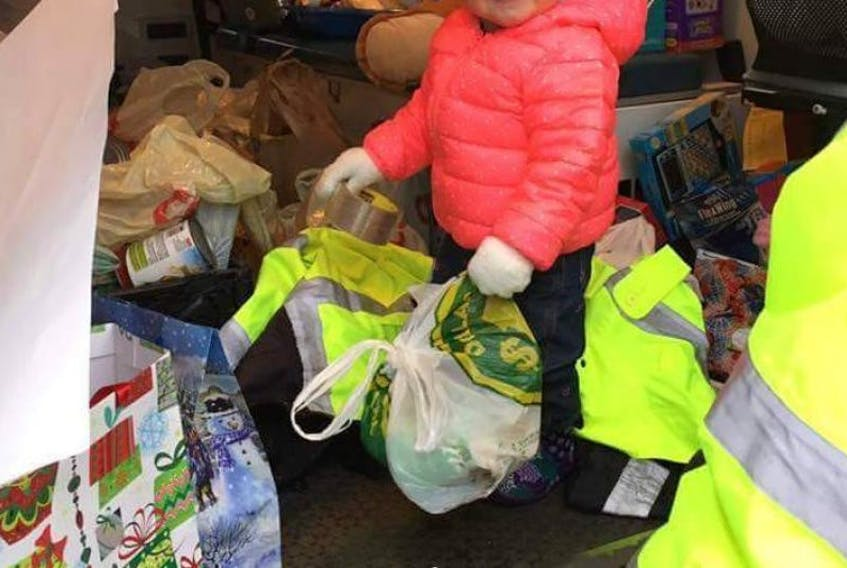 Lilly Mills was all smiles as she gave her Mom, Chrissy, a primary care paramedic, a helping hand during the fifth annual Freake's Ambulance toy and food bank drive on Nov. 26 in Lewisporte. Volunteers said it was one of best years to date for donations.