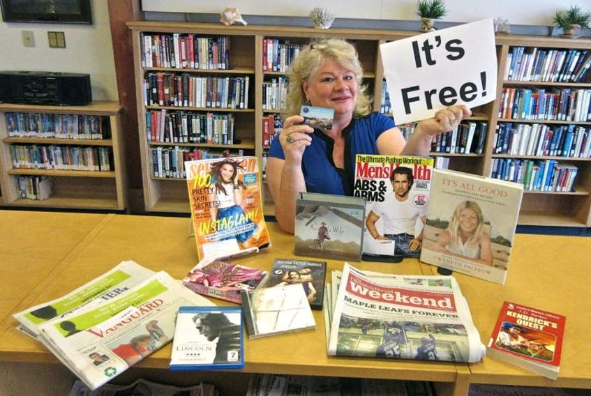 Library clerk Janet Miller holds a library card behind a display of a wide variety of library items available at the library. Library Card Month celebrates the public library and library users have a chance to win prizes.