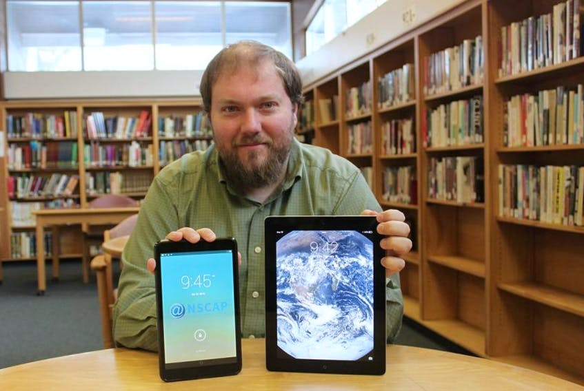 <p>Ryan McKenzie, coordinator for South West Nova Community Access Society, holds Apple and Alcatel tablets available at Western Counties Regional Library branches for hands-on training for older adults in mobile technology.</p>
