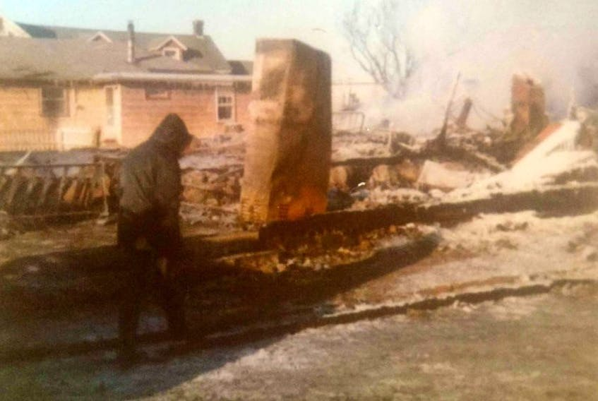 A person walks past the smouldering ruins in Lockeport after the Feb. 3, 1975 fire.