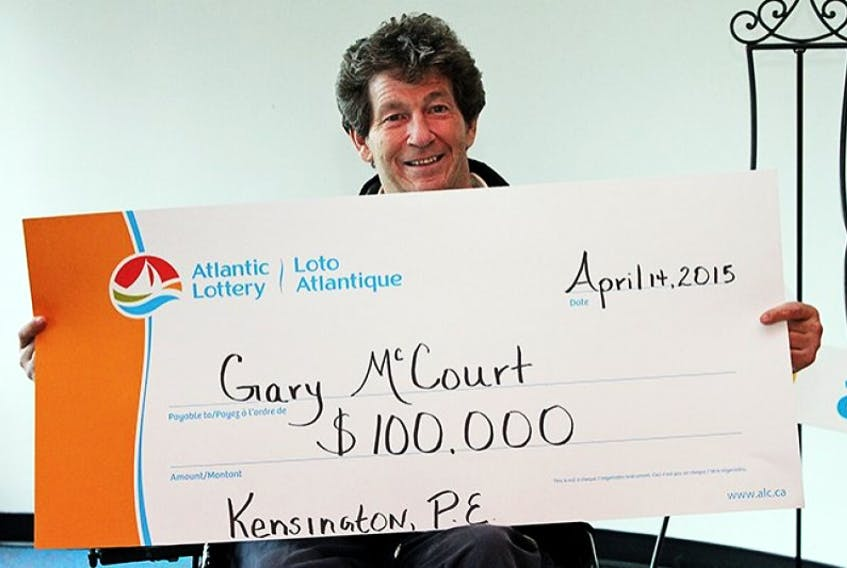 Gary McCourt of Kensington holds a symbolic cheque representing his $100,000 Atlantic Lottery win in this photo provided by the corporation.