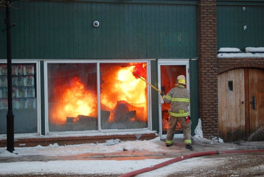 Firefighter Craig Harnum uses a long-handled pick to break out a window in Happy Warriors Yoga to give other firefighters an opportunity to spray water on the fire inside the 104 Main St. building fire in Stephenville on Friday.