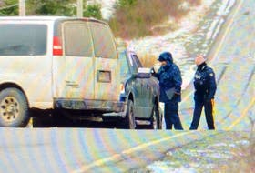 Police examine a pickup truck that was parked in the middle of the road with its emergency lights blinking Friday. Officers closed off a portion of Route 10 south of La Manche and north of Cape Broyle as they investigated the scene. It's not known how the scene is linked to the murder in Renews. — KEITH GOSSE/The Telegram