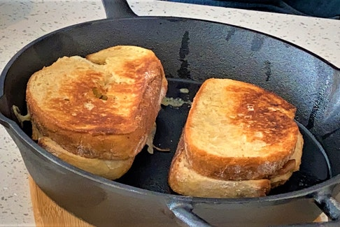 Mark DeWolf sears his Ultimate Grilled Cheese sandwich, featuring cheddar and bacon jam, in a cast iron pan.