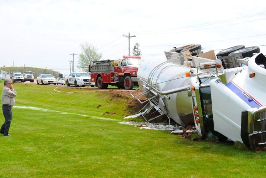 ADL's Thane MacEwen surveys the damage to one of the company's fleet of milk trucks that went off the road around 1:30 p.m. Thursday.