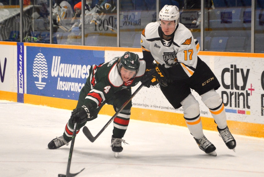 Jake Furlong of the Halifax Mooseheads, left, pokes the puck away from Cole Fraser of the Cape Breton Eagles during Quebec Major Junior Hockey League action at Centre 200 in Sydney on Tuesday. Halifax won the game 4-3 in overtime. (JEREMY FRASER/SALTWIRE NETWORK)