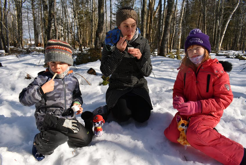 Anna Keenan, her son Oscar Keenan-Hamon, 5, and family friend Violet Van Toever, 7, enjoy some samples of homemade maple syrup on Saturday at the 2021 P.E.I. Winter Woodlot Tour.