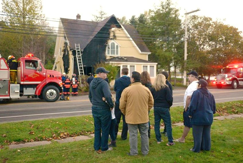 George Mardini (in brown coat) and members of his family watch as firefighters try to put down a fire in his home on Main Street in Mount Stewart Monday. His wife suffered some burns and was taken to the QEH.