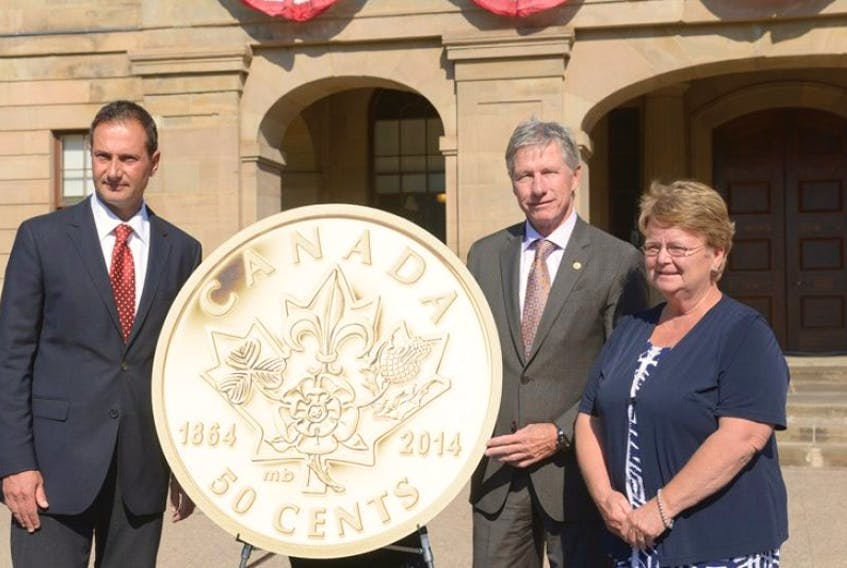 Premier Robert Ghiz, left, Marc Brule, chief financial officer for the Royal Canadian Mint and Gail Shea, minister of fisheries and oceans and Egmont MP, unveil the new coin minted to commemorate the 150th anniversary of the Charlottetown and Quebec Conferences. The coin was unveiled on the steps of Province House Tuesday.