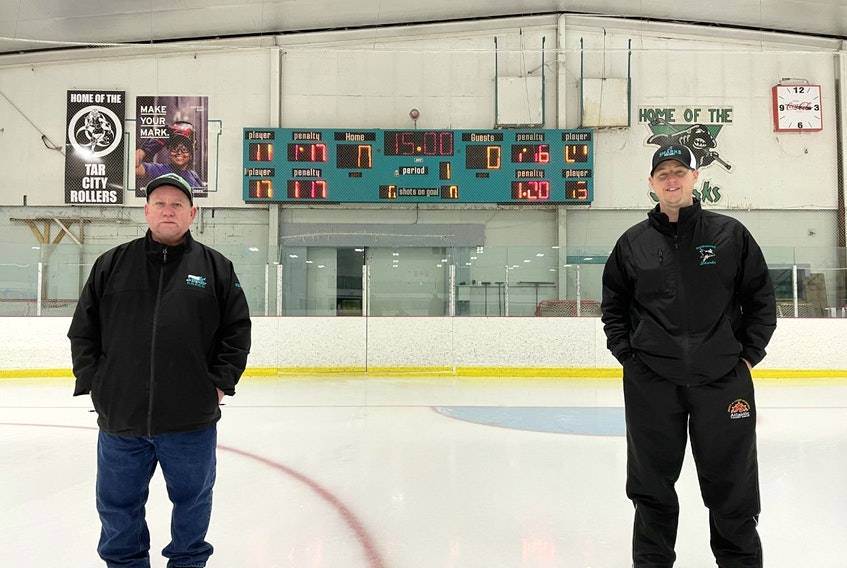 New Waterford and District Community Centre manager Kevin Forward, left, and Kyle Baldwin, president of the New Waterford Minor Hockey Association, are shown in front of the venue's time clock on Tuesday. Both the community centre and minor hockey association have come together to fundraise in an effort to get a new clock in time for the 2021-22 season. JERMEY FRASER/CAPE BRETON POST
