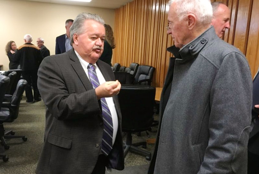 Minister of Natural Resources Lloyd Hines, speaks with former Premier John Hamm at a gathering Thursday at the Pictou County Chamber of Commerce.