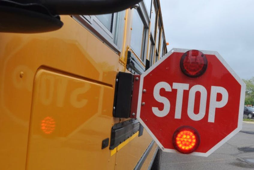 A school bus with its stop sign out and lights flashing.