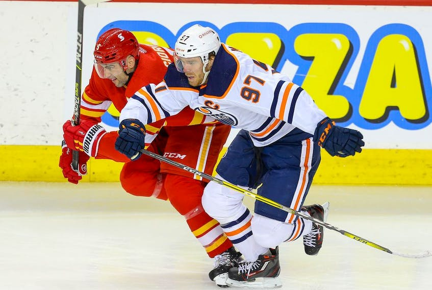 The Calgary Flames' Mark Giordano gets in a foot race with the Edmonton OIlers' Connor McDavid at the Saddledome in Calgary on Friday, Feb. 19, 2021.