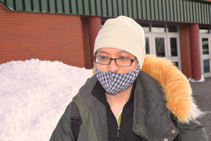 Vo Phuc, originally of China, currently living in Sydney and attending Cape Breton University, heads to class on the campus Tuesday. Phuc said he wears a surgical mask to keep his face warm but also becasue he believes it protects from viruses, The masks are getting harder to find as Chinese people in Cape Breton say they are desperately searching for them to mail home to family in China, where due to the outbreak of the coronavirus, the masks can't be found right now. Sharon Montgomery-Dupe/Cape Breton Post
