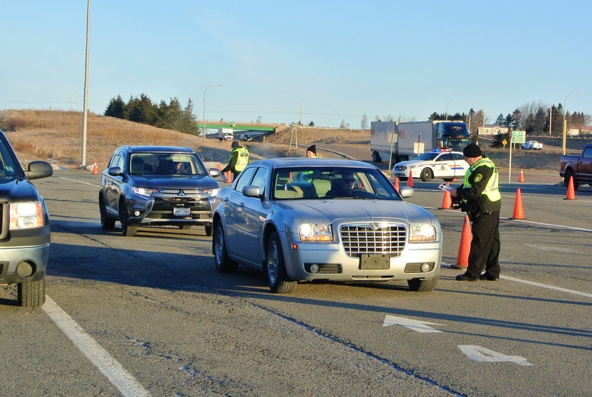 Provincial officials question motorists as they enter Nova Scotia at the inbound weigh scale in Fort Lawrence early Monday. RCMP were on hand to assist provincial officials as they tighten the border as a result of the province's state of emergency declaration. DARRELL COLE/SALTWIRE NETWORK