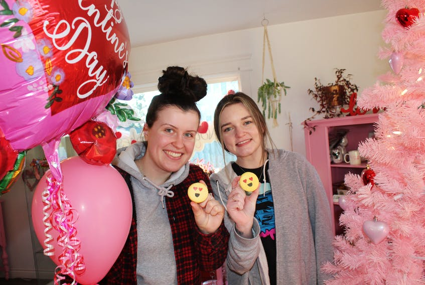 Aislinn MacIsaac, left, and Chelsea Parsons, front shop staff at Not Just Cakes Sweet Studio in Sydney River show off some emoji macarons that have been hot sellers at the dessert shop. Business has been good heading into Valentine's Day. GREG MCNEIL/CAPE BRETON POST