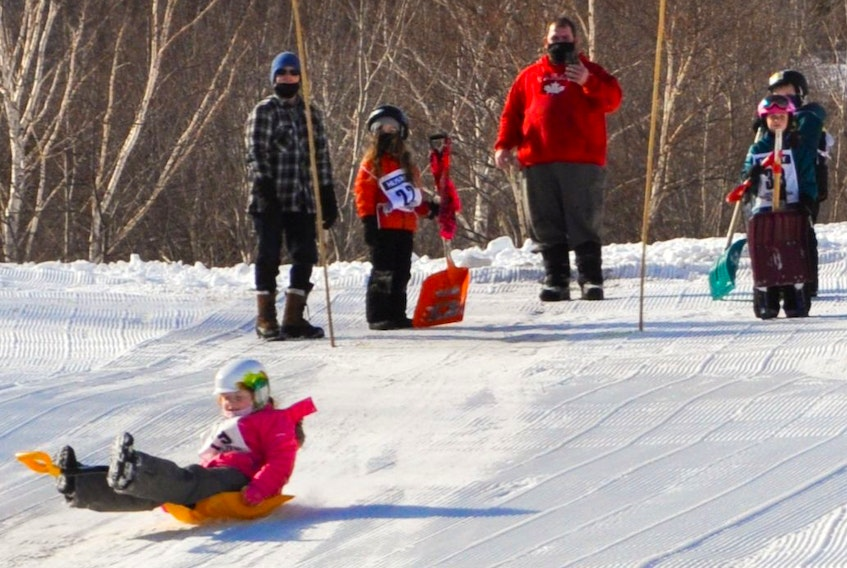 There's more to Cape Smokey than just skiing and snowboarding as evidenced by a recent downhill shovel race. Above, a young participant slides down the hill on a bright, orange shovel. CONTRIBUTED