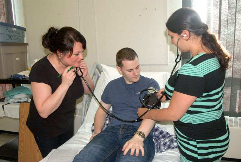Petrina Bartlett (left) and Melanie Acreman (right) practice taking the blood pressure of fellow student Adam Loder.