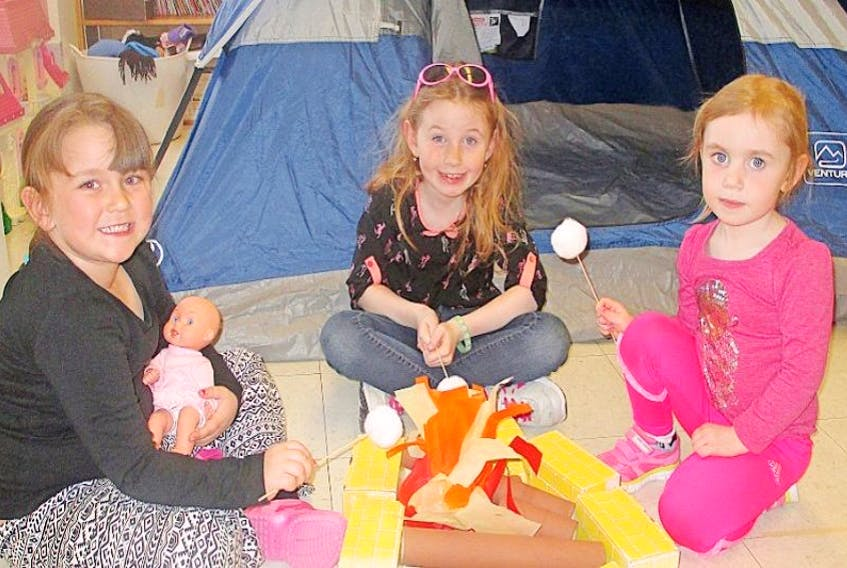 """The children at the Family Resource Centre, Outreach Site in Cook's Harbour used their imaginations for pretending camping outing recently. In the above picture children are pretending to be roasting marshmallows and singing campfire songs. They recently finished a four-week program """"Just Imagine"""", where participants use their imaginations to go on different adventures each week. The Outreach site is open on Wednesday evenings from 6:30pm to 8:30pm and is located in James Cook Memorial School"""