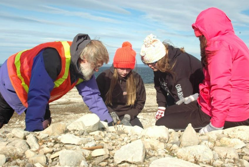 Michael Burzynski (left) showed several students from Canon Richards Memorial Academy how to dig up vegetation for transfer. Those who were a part of the discussion were, from left, Aleshia White, Kolbi Pilgrim and Tori Way.