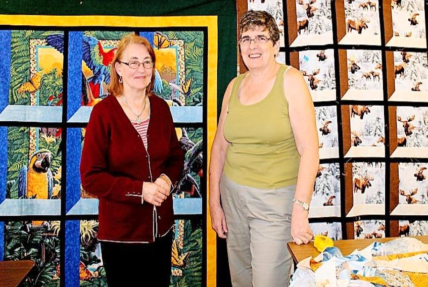 """Long Island Quilters quilting leader, Madeline Burton, arranged to have talented, veteran quilter, Daphne Thompson attend this week's session and instruct on how to make an """"attic window"""" quilt pattern. Two of Daphne's attic window quilts are in the backdrop."""