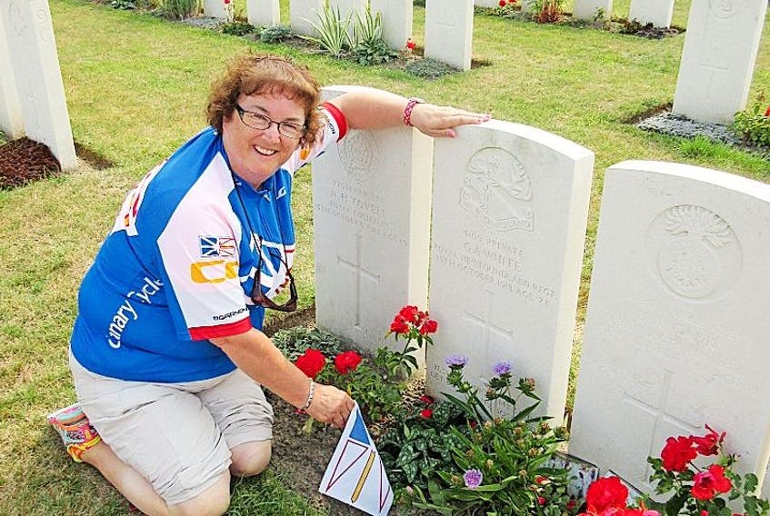 Golda Oxford of Springdale places a Newfoundland flag on the graveside of Pte. Gordon White's, her husband Lewis' great uncle and son of James and Elizabeth Ann White. He died in Belgium at the age of 28 during the First World War.