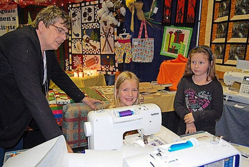 Daphne Thompson demonstrated to eight-year-old Katelyn Morgan and seven-year-old Jersey Young how to embroider their names using a special sewing machine.