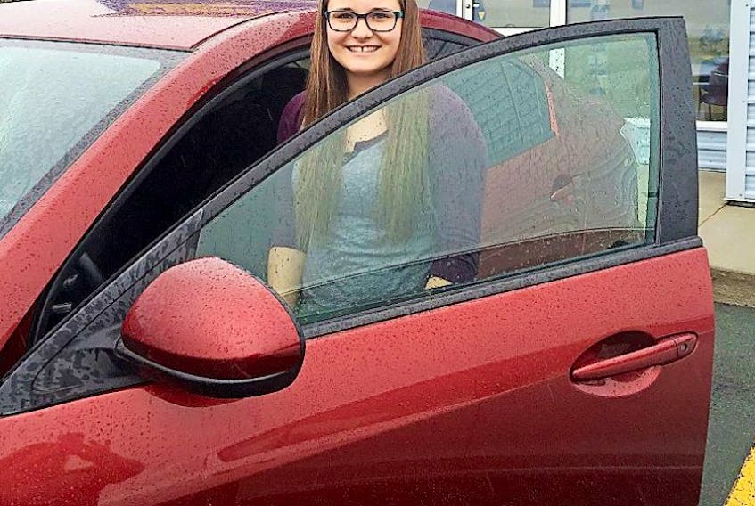 So happy to have been able to replace her 2010 Mazda 3, Kelsey Oxford poses with her new car following a write-off of her older one.