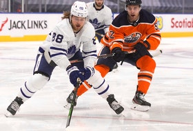The Edmonton Oilers' Patrick Russell (52) chases the Toronto Maple Leafs' William Nylander (88) during second period NHL action at Rogers Place, in Edmonton Saturday Feb. 27, 2021.