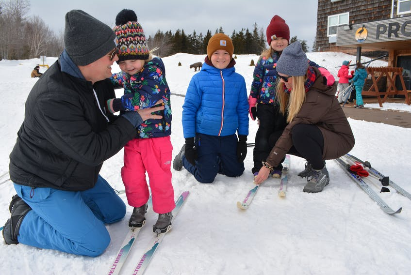 Thatcher MacKay, center, watches as his parents, Andrew and Robyn, assists his sisters, Elliott, second left, and Everleigh with their skis. Fears over the coronavirus led to the Cape Traverse family cancelling their March Break excursion to Halifax in favour of an outing closer to home. Eric McCarthy/Journal Pioneer