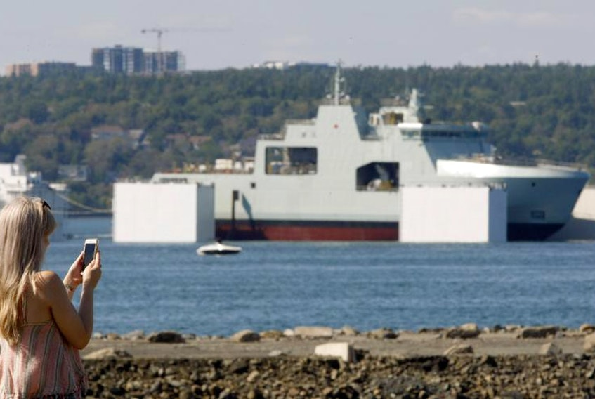 A spectator at the Africville Museum Baptist church grounds takes a photo of the Bedford Basin as the float test for the Future HMCS Harry DeWolf gets underway Saturday afternoon.