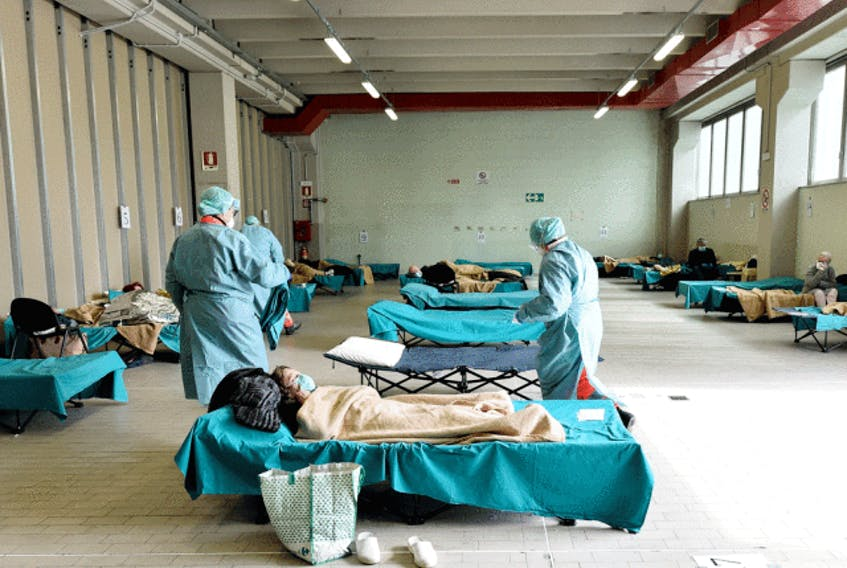 Medical personnel care for patients in an emergency temporary room, set up to ease pressure on the healthcare system caused by the coronavirus pandemic, at a hospital in Brescia, Italy, on March 13, 2020.