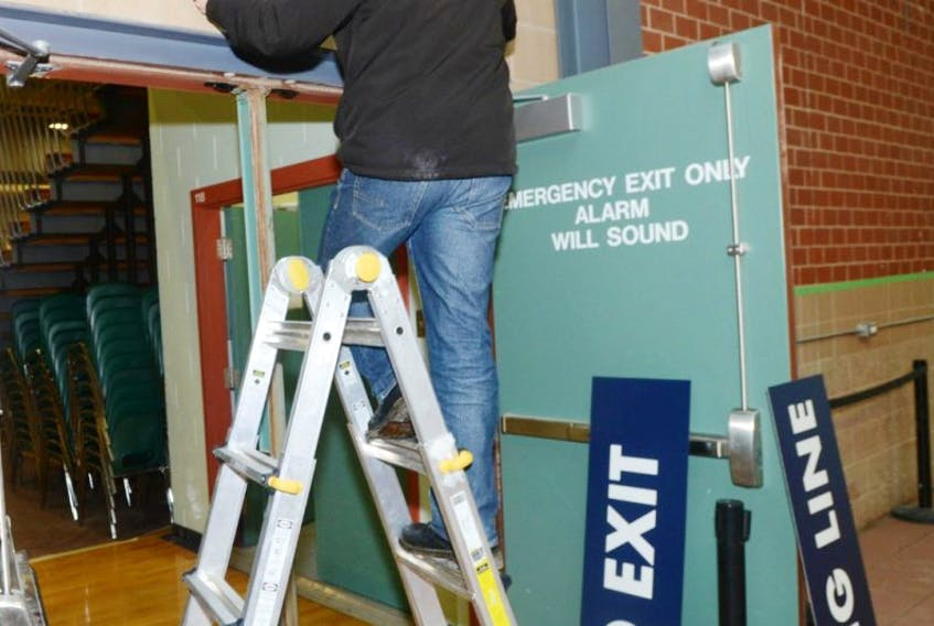 Chuck Gillis, of Yesco, hangs signage at the Chi-Wan Young Sports Centre at UPEI in preparation of today's PC leadership convention in Charlottetown.
