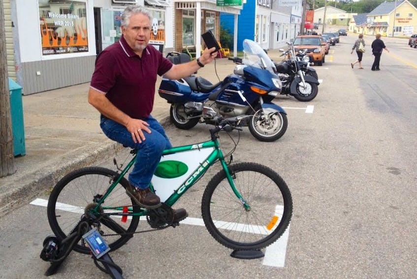 <p>Terry Thibodeau charges his cellphone with peddle-power. The charger will be set up downtown on Saturday and Sunday of the Wharf Rat Rally to help spread the word about the upcoming Digby Clare Renewable Energy Symposium.</p>