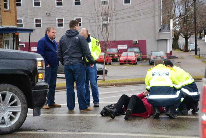 Paramedics treat a woman who was hit in a crosswalk at the intersection of George and Dorchester streets in Sydney, Thursday.