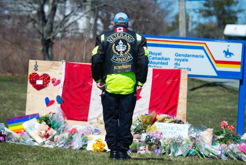 Former RCMP and naval officer Gerry White stands at attention in front of a memorial to fallen RCMP officer Const. Heidi Stevenson outside the Enfield RCMP detachment in Nova Scotia on Tuesday.