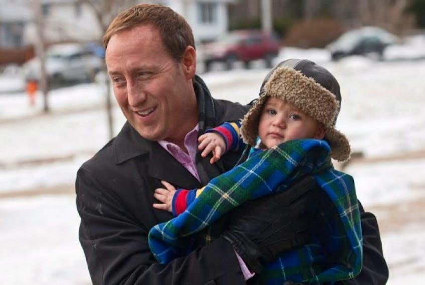 Peter MacKay holds his son Kian in Halifax. FILE