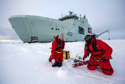 Civilian contractors conduct ice measurement operations alongside HMCS Harry DeWolf during cold weather trials near Frobisher Bay on Feb. 20, 2021. Cpl. David Veldman -  Canadian Armed Forces