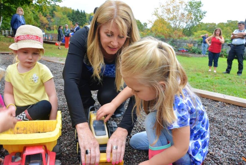 Tina Mundy, centre, plays with a group of four-year-olds at Precious Lambs Early Childhood Centre. Mundy, the minister of Family and Human Services announced a $300,000 investment to the childcare subsidy program on Thursday.
